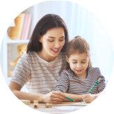 teacher assisting little girl to write