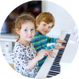 two children learning piano