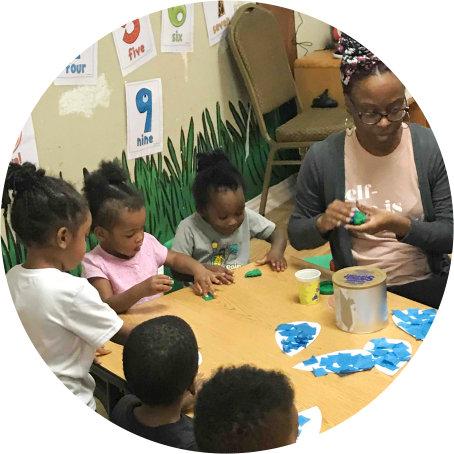 group of children and a teacher doing artwork